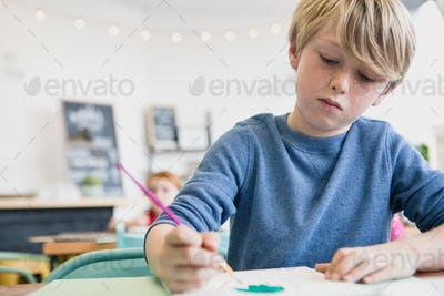 Boy Painting in Class