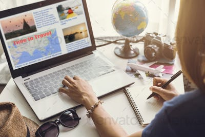 Young women planning vacation trip and searching information