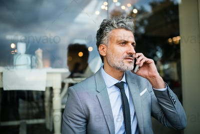 Businessman with smartphone in an outdoor hotel cafe.