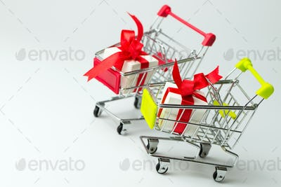 White gift box tied with red ribbon in two shopping carts
