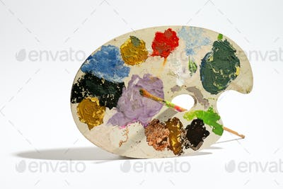 Painting palette with brush on white background