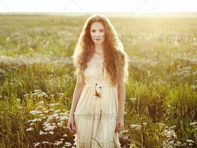 Young beautiful girl on a summer field. Beauty summertime