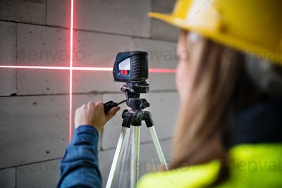 Young woman worker with laser on the building site.