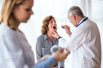 Senior doctor examining a senior woman in office.