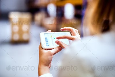 Woman warehouse worker with smartphone.