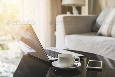 Laptop computer with smart phone and cup of coffee