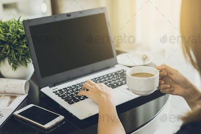 woman's hands typing on a laptop keyboard with cup of coffee