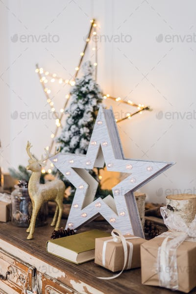 winter still life with Christmas decorations toy deer, star and gift boxes on light background. soft