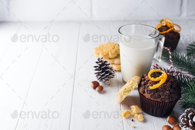 Freshly baked homemade chocolate muffins with jug with milk