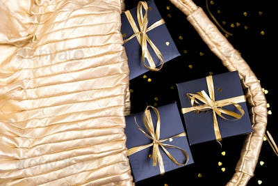 Black gift boxes with gold ribbon pop out from golden bag on shine background. Flat lay.