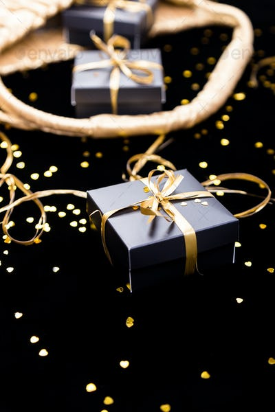 Black gift boxes with gold ribbon pop out from golden bag on shine background. Close up.