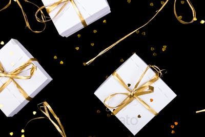 White gift boxes with gold ribbon on shine background. Flat lay