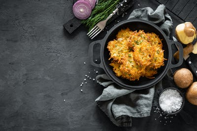 Potato pancakes on dark background, top view