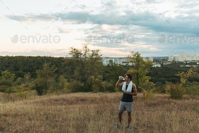 Healthy man drinking water on nature while resting