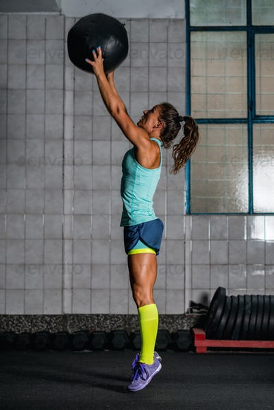 Woman athlete exercising with medicine ball