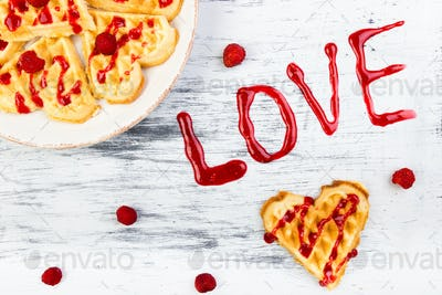 Belgian heart shaped waffle on white background. Word love made by jam.