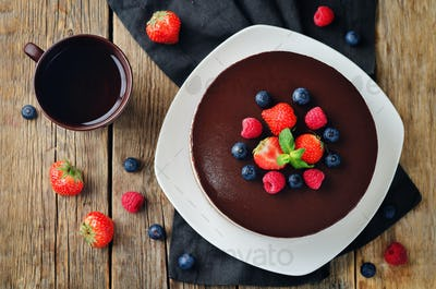 Triple chocolate mousse cake decorated with fresh berries.