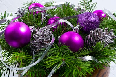 Christmas arrangement with purple balls in the wooden bowl