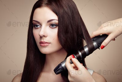 Hairdresser woman curls her hair