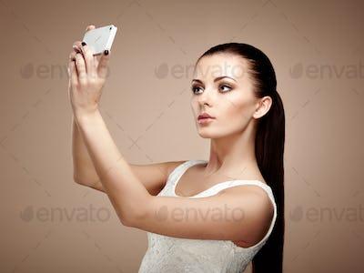 Beautiful young woman taking selfie