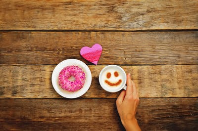 Wood background with cup of coffee, donut, heart and woman's han