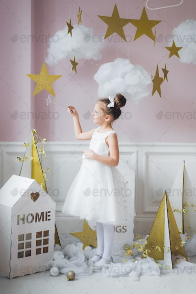 Adorable little fairy girl with magic wand at christmas decorations indoors
