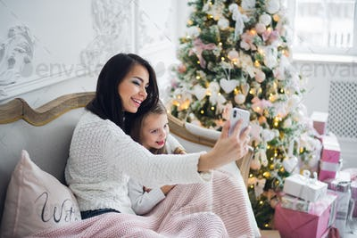 Well-groomed hand of a woman holding a phone taking a selfie with her daughter, little girl