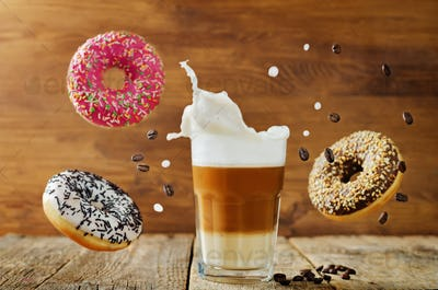 Flying multicolored donuts with a glass of coffee