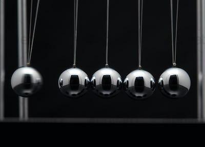 Closeup Of Newton Cradle With Swinging Metal Balls
