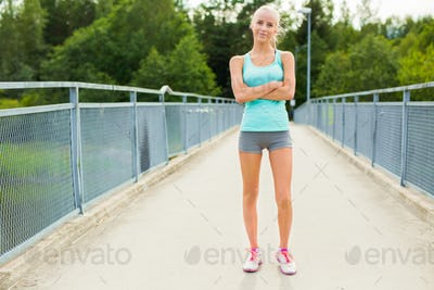 Confident and smiling young female runner having break after workout