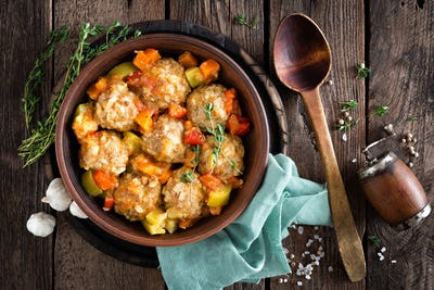 Meatballs stewed with vegetables on wooden table, top view