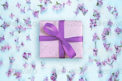 Gift box and lilac flowers on blue background