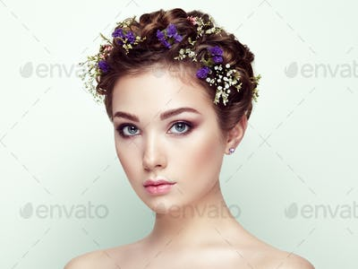 Face of beautiful woman decorated with flowers