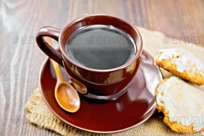 Coffee in brown cup with cookies on dark board