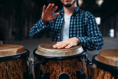 Drummer hands playing on wooden drum, closeup