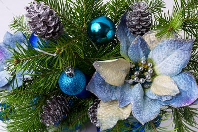 Christmas arrangement with fir branches and blue silk poinsettia