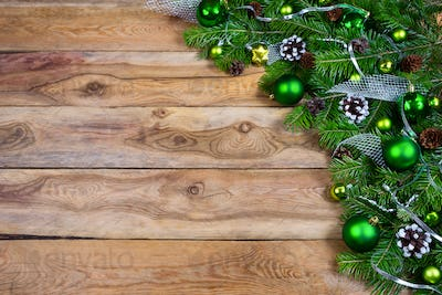 Christmas garland with green baubles on the wooden background, c