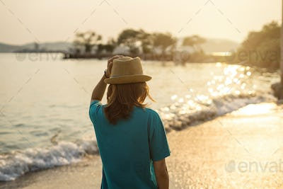 Young woman traveler walking on the beach at sunset