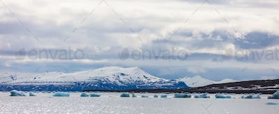 Panorama of floating sea ice in front of snowy mountains in the arctic