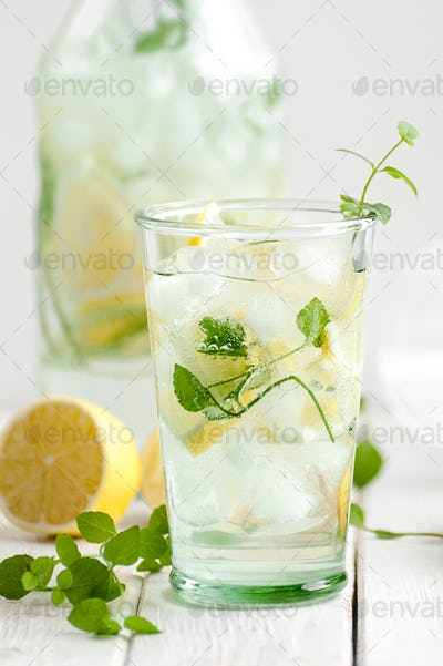 Citrus lemonade in a glass cup on a white wooden table close-up.
