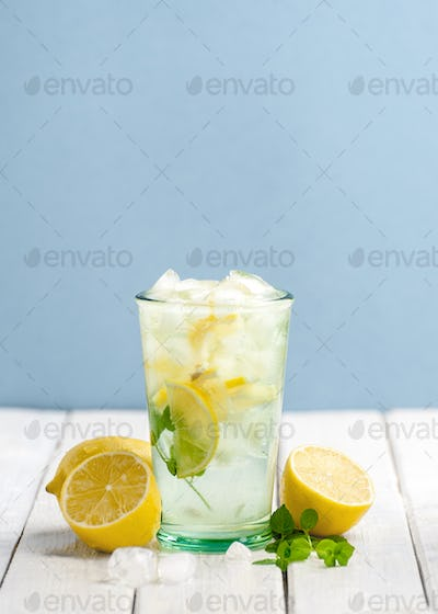 Cold lemonade and fresh lemons on a white wooden table on a blue
