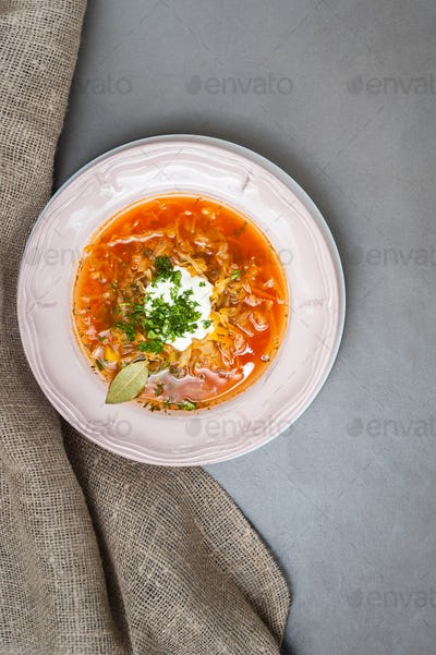 Russian cabbage soup in a vintage plate on a gray stone table.