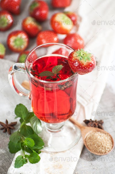Freshly brewed cup of strawberry tea with fresh mint.