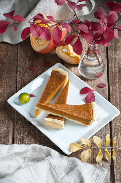 Three slices of pumpkin pie on a white plate.