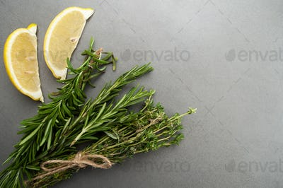 Fresh rosemary, thyme and two slices of lemon on a gray stone ta
