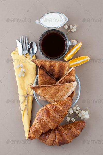 Black coffee, milk, croissants and toast close-up on a light bro