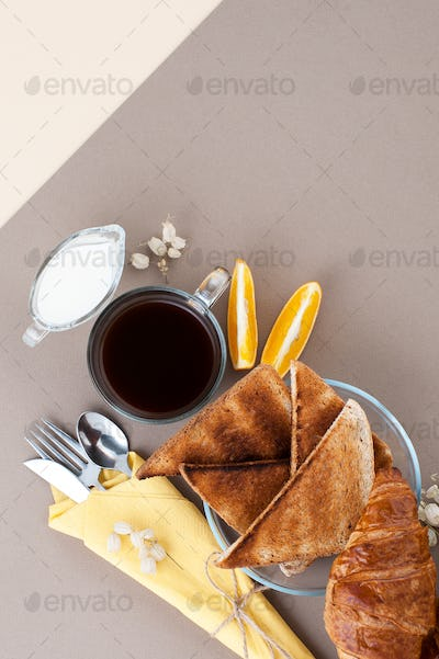 Black coffee, cream, fresh croissants and toasts are served on a