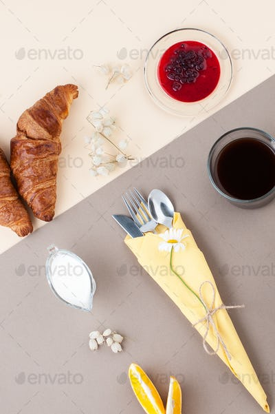 Black coffee, milk, croissants, jam and fresh fruit on a light y