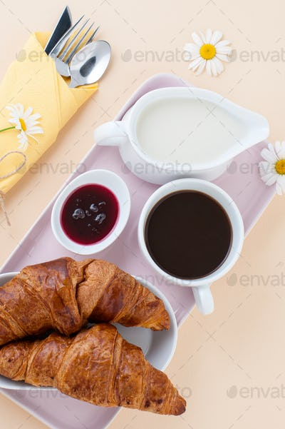 Breakfast consisting of black coffee, milk and a croissant with