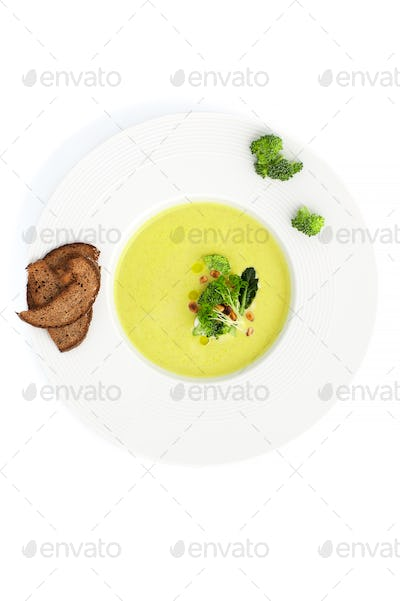 Green cream soup of broccoli and croutons close-up in a white pl